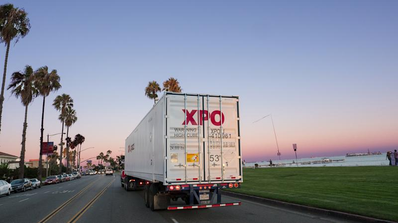 An XPO truck on the road near water, surrounded by palm trees and blue sky