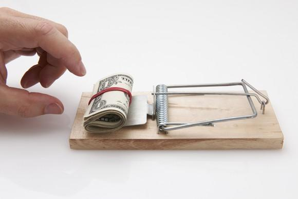 Hand reaching for money used as bait in a mousetrap.