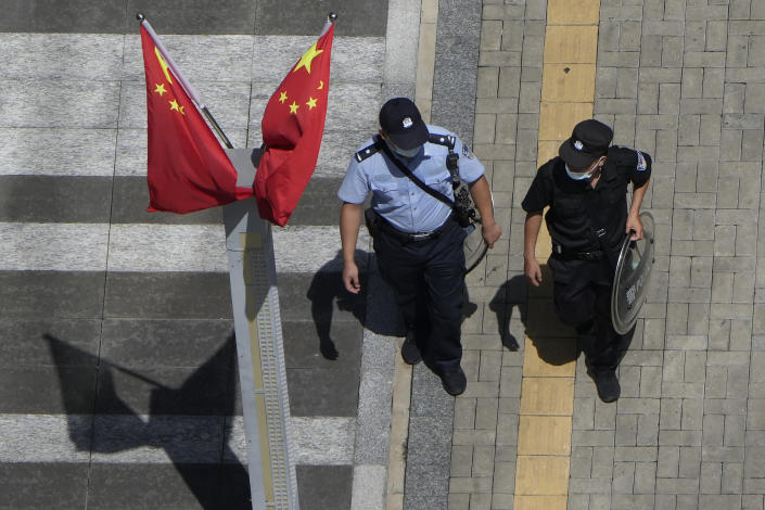 A policeman, right, and security guard walk past Chinese flags outside the Evergrande headquarters in Shenzhen, China, Friday, Sept. 24, 2021. Things appeared quiet at the headquarters of the heavily indebted Chinese real estate developer Evergrande, one day after the day it had promised to pay interest due to bondholders in China. (AP Photo/Ng Han Guan)