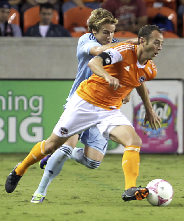 Sporting Kansas City's Chance Myers, left, holds on to Houston Dynamo midfielder Brad Davis, right, during the first half of an MLS soccer game Wednesday, Oct. 9, 2013, in Houston. (AP Photo/Houston Chronicle, James Nielsen)