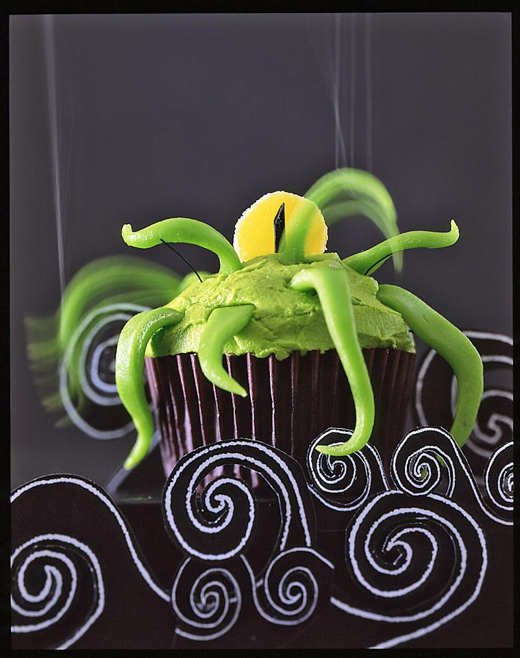 """<p>An alien arrives by sea, warding off all who come near with his flailing taffy tentacles. Spread our <a href=""""https://www.marthastewart.com/1139180/one-bowl-chocolate-cupcakes"""">One-Bowl Chocolate Cupcakes</a> with a thin layer of&nbsp;<a href=""""https://www.marthastewart.com/353415/swiss-meringue-buttercream"""">Swiss Meringue Buttercream</a> tinted with a few drops of green food coloring. Cut strips of green taffy and attach around top of <a href=""""https://www.marthastewart.com/275387/classic-cupcakes"""">cupcake</a>. For its eye, slice a yellow gumdrop in half and press into top of cupcake. A piece of black licorice attached in front of the gumdrop completes the creepy gaze.</p>"""