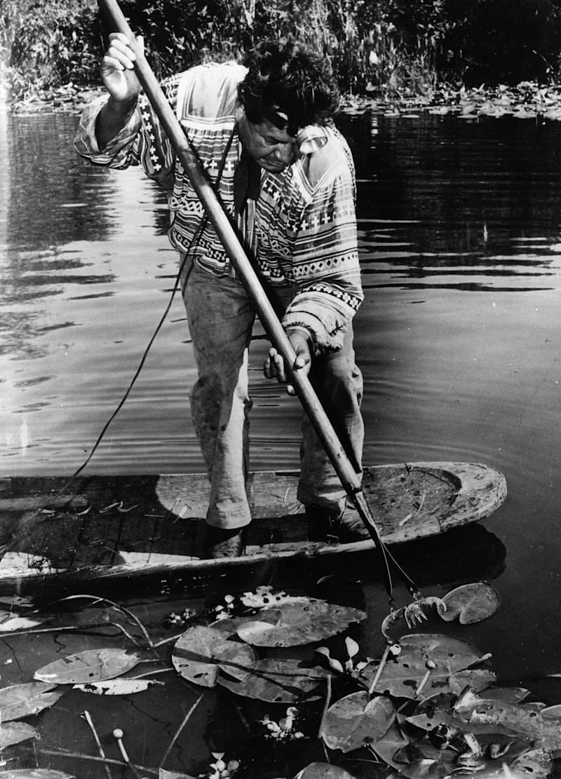 Native American Seminole chief Willie Osoeola balances on a dugout canoe in the1940s while hunting frogs that he'd sell to hotels and restaurants. (Keystone via Getty Images)
