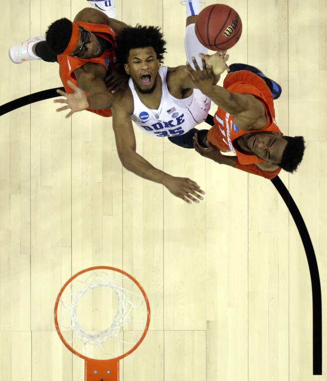 Duke's Marvin Bagley III, center, shoots as Syracuse's Oshae Brissett, right, and Paschal Chukwu defend during the first half of a regional semifinal game in the NCAA men's college basketball tournament Friday, March 23, 2018, in Omaha, Neb. (AP Photo/Charlie Neibergall)