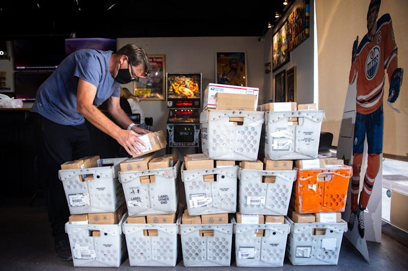 Mike Jaspersen, cofounder of Jaspy's Case Breaks, prepares boxes of sports cards for shipment to customers.