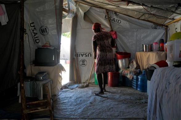 Earthquake survivor Aline Deispeines, 44, sweeps the floor of her tent home located near the headquarters of her Organization of Dedicated Women in Action in Port-au-Prince, March 4, 2012.