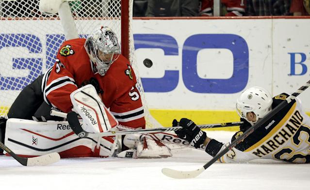 Chicago Blackhawks goalie Corey Crawford (50), left, blocks a shot by Boston Bruins' Brad Marchand (63) during the first period of an NHL hockey game in Chicago, Sunday, Jan. 19, 2014. (AP Photo/Nam Y. Huh)