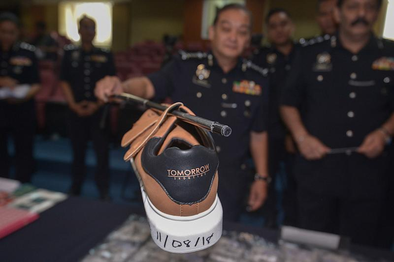 Selangor police chief Datuk Mazlan Mansor shows how the drug mules operate during a press conference at IPK Selangor in Shah Alam, August 20, 2018. — Picture by Mukhriz Hazim