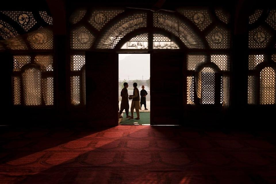 Afghan students walk out of the mosque at the Khatamul Anbiya madrasa after morning prayers in Kabul, Afghanistan (AP)
