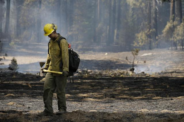 Firefighter Troy Drouin takes a short break before mopping up hot spots near Yosemite National Park, Calif., on Wednesday, Aug. 28, 2013. The giant wildfire burning at the edge of Yosemite National Park is 23 percent contained, U.S. fire officials said Wednesday. (AP Photo/Jae C. Hong)