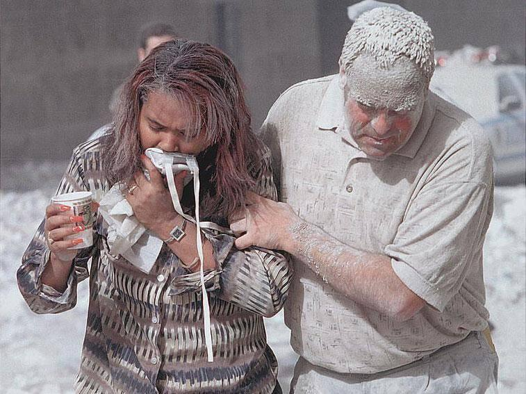 Man covered with ashes assisting a woman walking and holding a particle mask to her face, following the attack (Don Halasy)