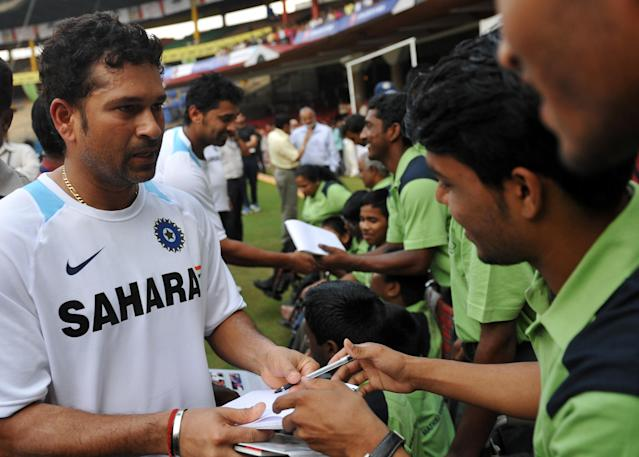 Indian cricketer Sachin Tendulkar signs autographs for fans after he became the first ever batsman to reach the millestone of 14000 Test runs during the second day of the second Test between India and Australia at M.Chinnaswamy Stadium in Bangalore on October 10, 2010. In reply to Australia's first innings of 478 runs India are 110 runs for the loss of two wickets in 27 overs. AFP PHOTO/Dibyangshu SARKAR (Photo credit should read DIBYANGSHU SARKAR/AFP/Getty Images)