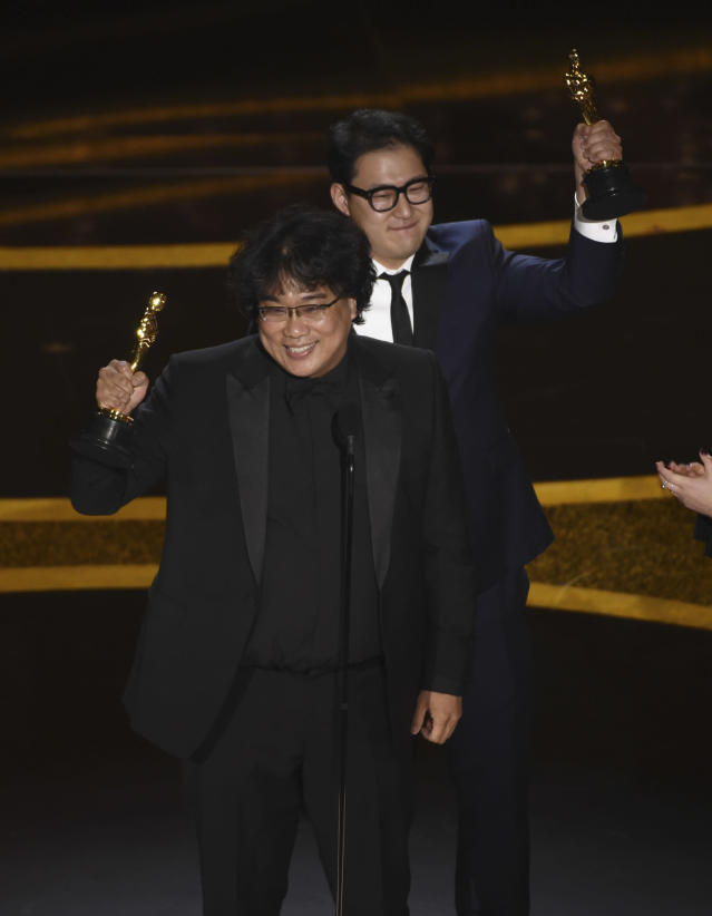 """Bong Joon Ho, left, and Han Jin Won accept the award for best original screenplay for """"Parasite"""" at the Oscars on Sunday, Feb. 9, 2020, at the Dolby Theatre in Los Angeles. (AP Photo/Chris Pizzello)"""
