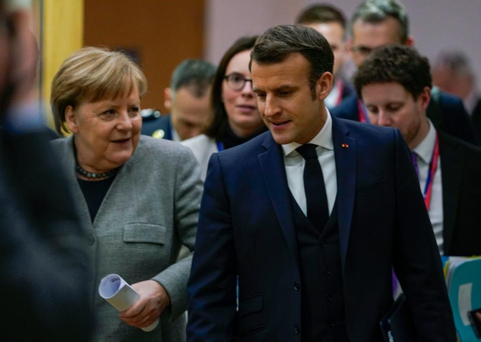 Germany's Chancellor Angela Merkel (L) and France's President Emmanuel Macron speak as they walk after a bi-lateral meeting on the second day of a special European Council summit in Brussels on February 21, 2020, held to discuss the next long-term budget of the European Union (EU). (Photo by kenzo tribouillard / POOL / AFP) (Photo by KENZO TRIBOUILLARD/POOL/AFP via Getty Images)