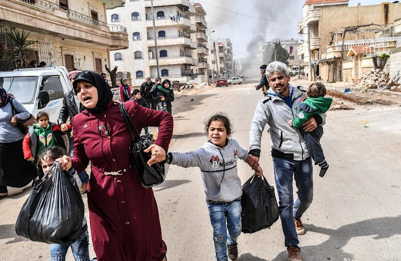 Civilians flee explosions in the city of Afrin in northern Syria on March 18, 2018, after Turkish forces and their rebel allies took control of the Kurdish-majority city (AFP Photo/Bulent Kilic)
