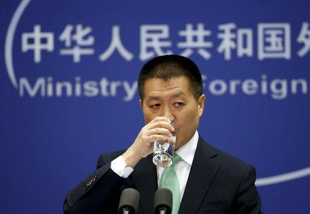 FILE PHOTO: Chinese Foreign Ministry spokesman Lu Kang drinks a cup of water at a regular news conference in Beijing