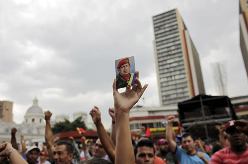 "A ""Chavista"" demonstrator, and supporter of President-elect Nicolas Maduro, holds a photo of the late President Hugo Chavez during a march in front of the National Electoral Council (CNE) in Caracas, Venezuela, Wednesday, April 17, 2013. Opposition candidate Henrique Capriles has presented a series of allegations of vote fraud and other irregularities to back up his demand for a vote-by-vote recount for the presidential election. Maduro, the hand-picked successor of the late Hugo Chavez, was declared the winner by 262,000 votes out of 14.9 million cast, and Capriles contends the purported abuses add up to more than Maduro's winning margin. (AP Photo/Ramon Espinosa)"