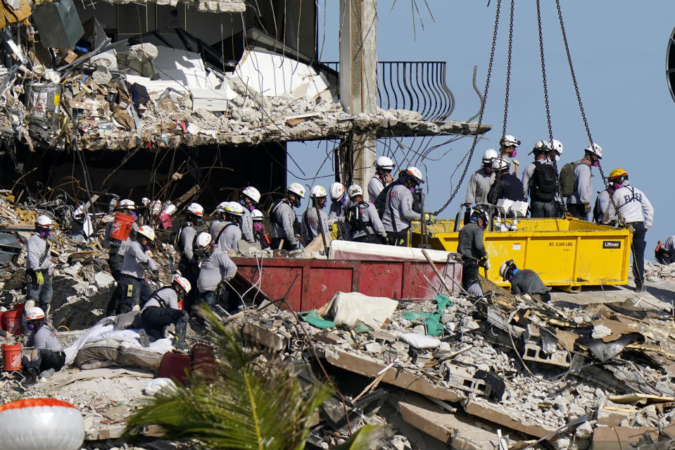 FILE - In this June 28, 2021, file photo, workers search the rubble at the Champlain Towers South Condo in Surfside, Fla. Search and rescue teams from Miami-Dade have been described as among the best and most experienced in the world. (AP Photo/Lynne Sladky, File)