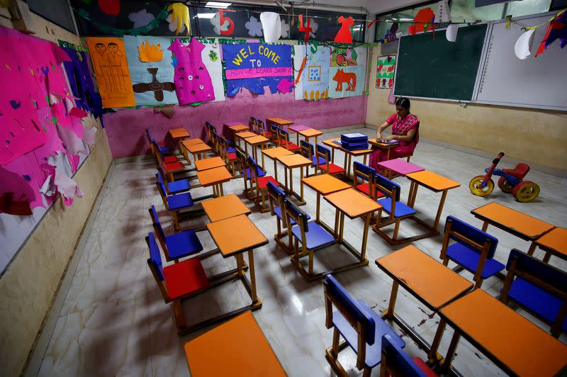 FILE PHOTO: A teacher sits in an empty classroom after Tamil Nadu state government ordered the closure of primary schools across the state amid coronavirus fears, in Chennai