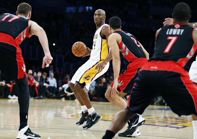 Los Angeles Lakers' Kobe Bryant dribbles the ball as he is guarded by Toronto Raptors' Landry Fields, second right, during the first quarter of an NBA basketball game in Los Angeles, Sunday, Dec. 8, 2013. (AP Photo/Danny Moloshok)