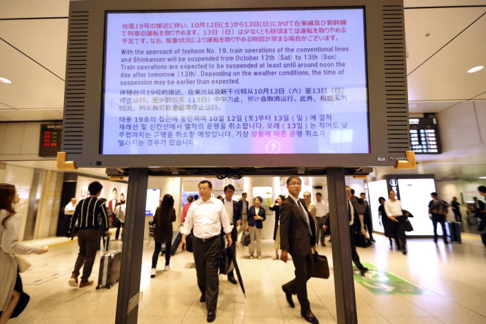 An electric board shows a notice on suspending operations of the Shinkansen or bullet train on Oct. 12-13 due to Typhoon Hagibis, at Tokyo Station in Tokyo Friday, Oct. 11, 2019. Japan's weather agency is warning a powerful typhoon may bring torrential rains to central Japan over the weekend. (AP Photo/Eugene Hoshiko)