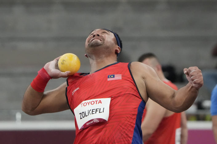FILE - In this Tuesday, Aug. 31, 2021, file photo, Muhammad Ziyad Zolkefli of Malaysia competes in the men's shot put F20 final during the Tokyo 2020 Paralympics Games at the National Stadium in Tokyo. Zolkefli appeared to have won gold in the shot put in the F20 class. But after the victory on Tuesday, he was disqualified because he had shown up late for the competition. (AP Photo/Eugene Hoshiko, File)