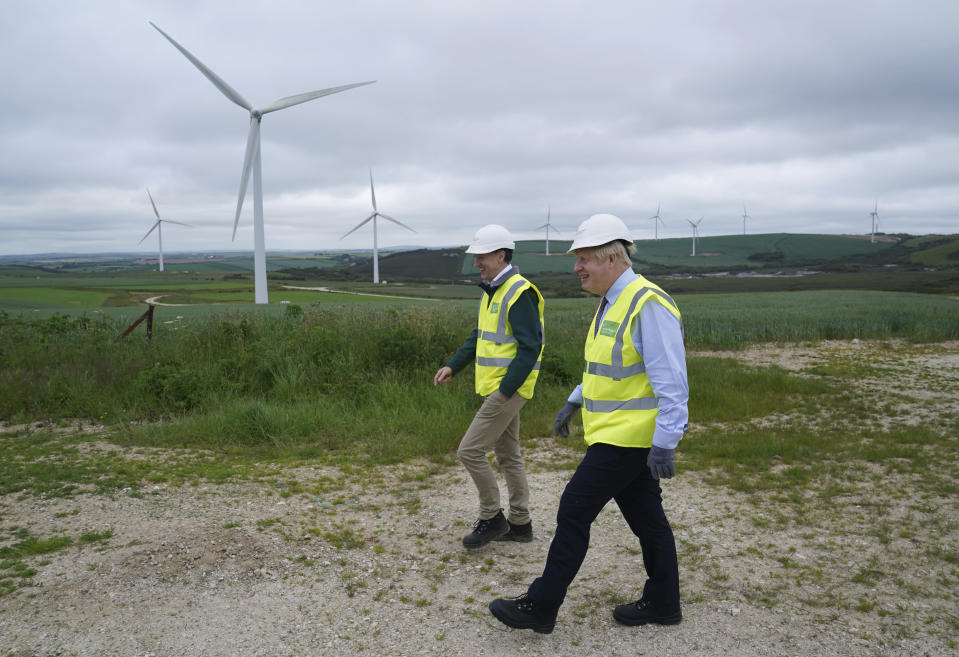 FILE - In this June 9, 2021, file photo, British Prime Minister Boris Johnson, right, visits the Scottish Power Carland Cross Windfarm to view new construction on a solar farm in Newquay, Cornwall, England. Leaders of some of the world's richest nations will be meeting at the English seaside for a three-day Group of Seven summit in a world that has changed hugely since their last gathering two years ago. Before the pandemic, Johnson planned this to be a climate-dominated summit. (AP Photo/Jon Super, Pool, File)