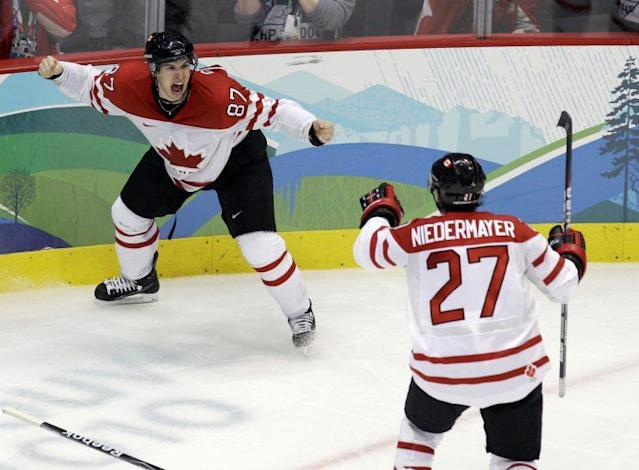 """Canada's <a class=""""link rapid-noclick-resp"""" href=""""/nhl/players/3737/"""" data-ylk=""""slk:Sidney Crosby"""">Sidney Crosby</a> (87) celebrates with Scott Niedermayer (27) after making the game-winning goal in the overtime period of a men's gold medal ice hockey game against USA at the Vancouver 2010 Olympics in Vancouver, British Columbia, Sunday, Feb. 28, 2010. Canada won 3-2. (AP Photo/Chris O'Meara)"""