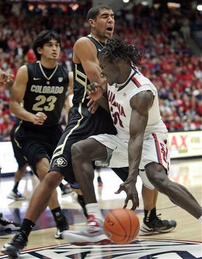 Arizona's Angelo Chol (30) drives against Colorado's Josh Scott, left, during the first half of an NCAA college basketball game at McKale Center in Tucson, Ariz., Thursday, Jan 3, 2013. (AP Photo/John Miller)