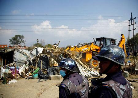 Nepalese police personnel stand guard as makeshift shelters are being demolished at the displacement camp for earthquake victims at Chuchepati in Kathmandu