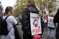 """A medical worker holds a placard reading : """"Money for Hospital, Not for the Capital, Our Solution Hospitals beds, Employs and quick"""", during a protest gathering outside the Health Ministry, in Paris, Tuesday, Sept. 14, 2021 against a law requiring them to get vaccinated by Wednesday or risk suspension from their jobs. The law is aimed at protecting patients from new surges of COVID-19. Most of the French population is vaccinated but a vocal minority are against the vaccine mandate. (AP Photo/Francois Mori)"""