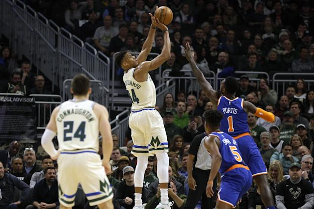 Milwaukee Bucks' Giannis Antetounmpo, center, shoots against the New York Knicks during the first half of an NBA basketball game Monday, Dec. 2, 2019, in Milwaukee. (AP Photo/Jeffrey Phelps)