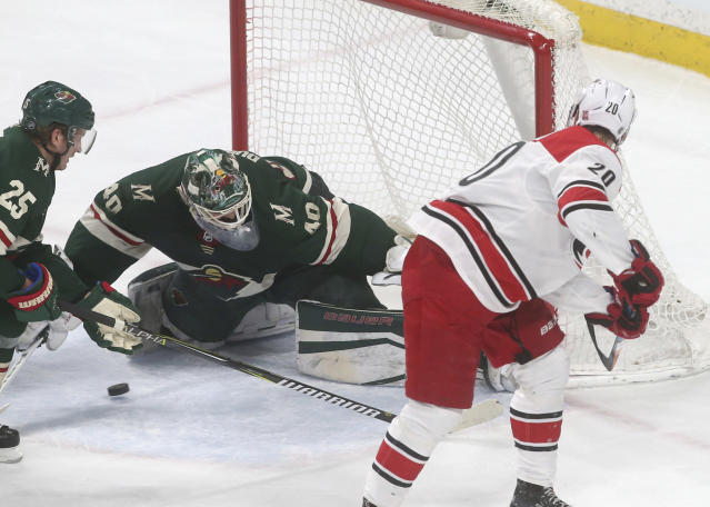 Minnesota Wild goalie Devan Dubnyk, left, stops a backhand shot by Carolina Hurricanes' Sebastian Aho during the first period of an NHL hockey game Tuesday, March 6, 2018, in St. Paul, Minn. (AP Photo/Jim Mone)