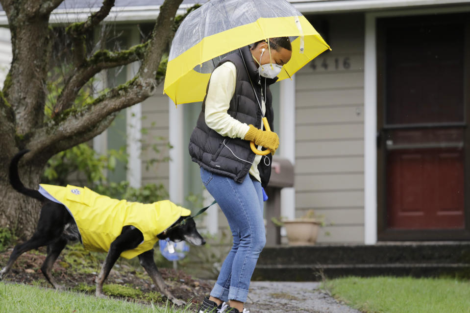 Dog walker Imaj Royster, wearing a protective mask as caution against the coronavirus outbreak, leads her charge Hazard during a stroll in the rain March 30, 2020, in Seattle. (AP Photo/Elaine Thompson)