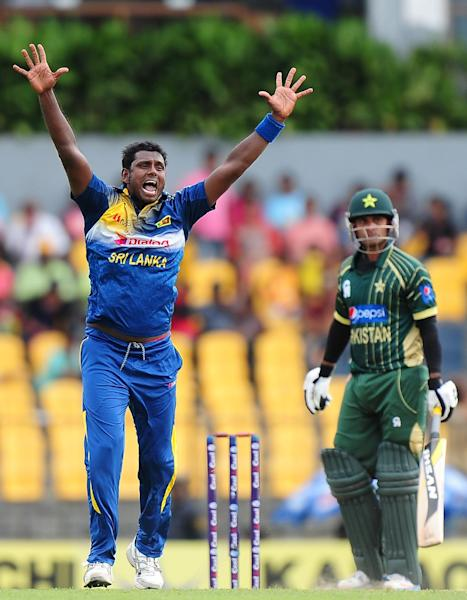 Sri Lanka's captain Angelo Mathews (L) appeals for a Leg Before Wicket decision against Pakistan batsman Mohammad Hafeez (R) during the first One Day International (ODI) match between Sri Lanka and Pakistan in Hambantota on August 23, 2014 (AFP Photo/Lakurwan Wanniarachchi)