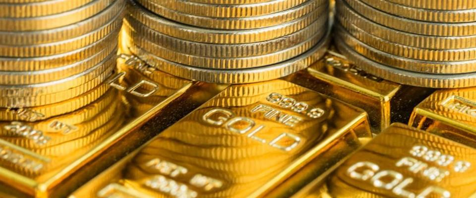closed up shot of shiny gold bars with stack of coins as business or financial investment and wealth concept.