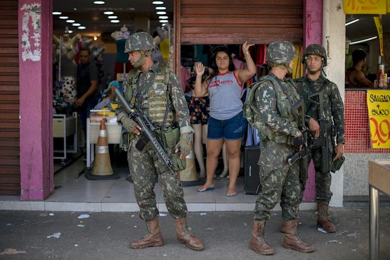 Brazilian soldiers stand guard in a high-crime Rio de Janeiro neighborhood in December