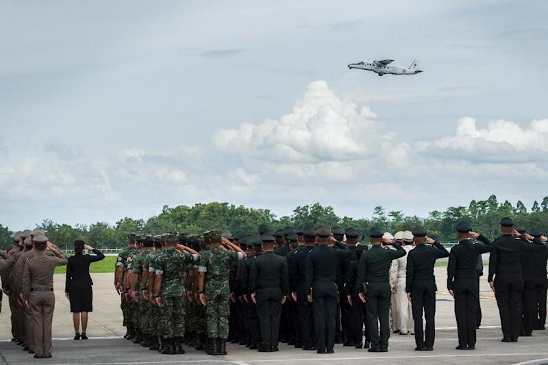 Thai soldiers and police officers pay their respects as a Thai Navy plane carrying the body of Saman Kunan (AFP Photo/YE AUNG THU)