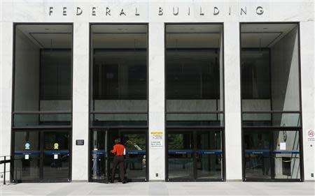A worker enters a transportation department federal building in Washington October 1, 2013. REUTERS/Kevin Lamarque