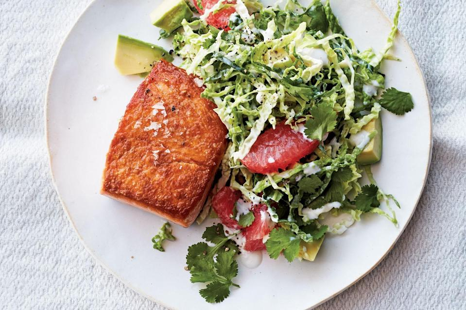 """This dish can help generate a little sunny feeling in the darkest days of winter. It's partly about the color story, with the pretty coral tones of the salmon and the grapefruit set against the pale green avocado. But there's also something beachy and Californian about the creamy cabbage slaw. <a href=""""https://www.epicurious.com/recipes/food/views/pan-roasted-salmon-with-grapefruit-cabbage-slaw?mbid=synd_yahoo_rss"""" rel=""""nofollow noopener"""" target=""""_blank"""" data-ylk=""""slk:See recipe."""" class=""""link rapid-noclick-resp"""">See recipe.</a>"""