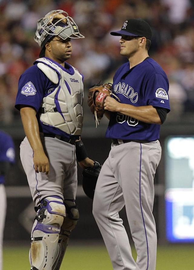 Colorado Rockies pitcher Jeff Manship confers with catcher Willin Rosario, left, after loading the bases in a baseball game against the Philadelphia Phillies, Monday, Aug. 19, 2013, in Philadelphia. (AP Photo/Laurence Kesterson)