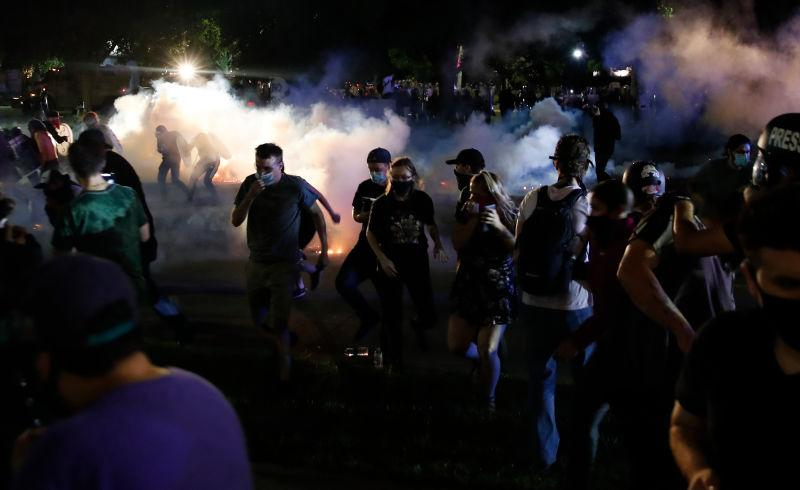 Protestors run for cover as police shoot tear gas in an effort to disperse the crowd outside the County Courthouse during demonstrations against the shooting of Jacob Blake in Kenosha, Wisconsin on August 25, 2020.