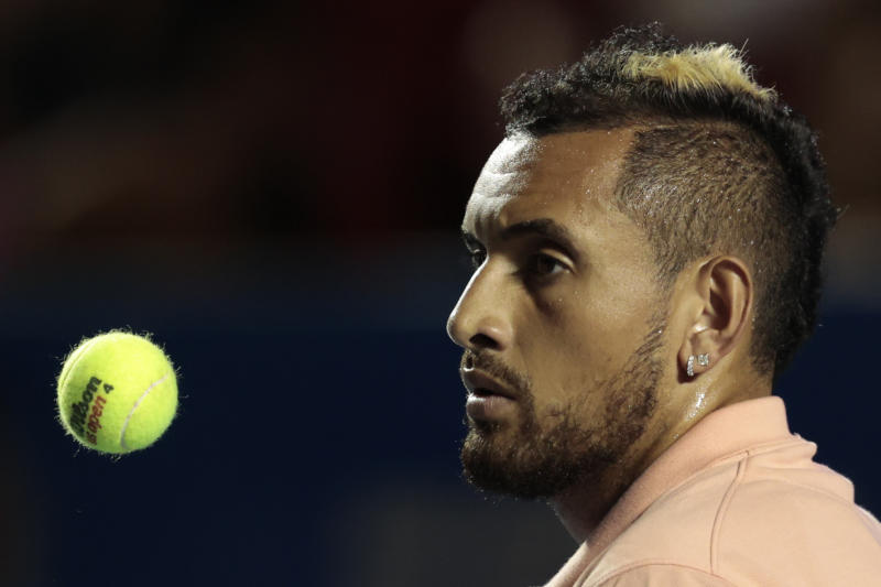 Australia's Nick Kyrgios tosses a ball in the air as he waits to serve, during his first round match against France's Ugo Humbert at the Mexican Tennis Open, in Acapulco, Mexico, Tuesday, Feb. 25, 2020.(AP Photo/Rebecca Blackwell)