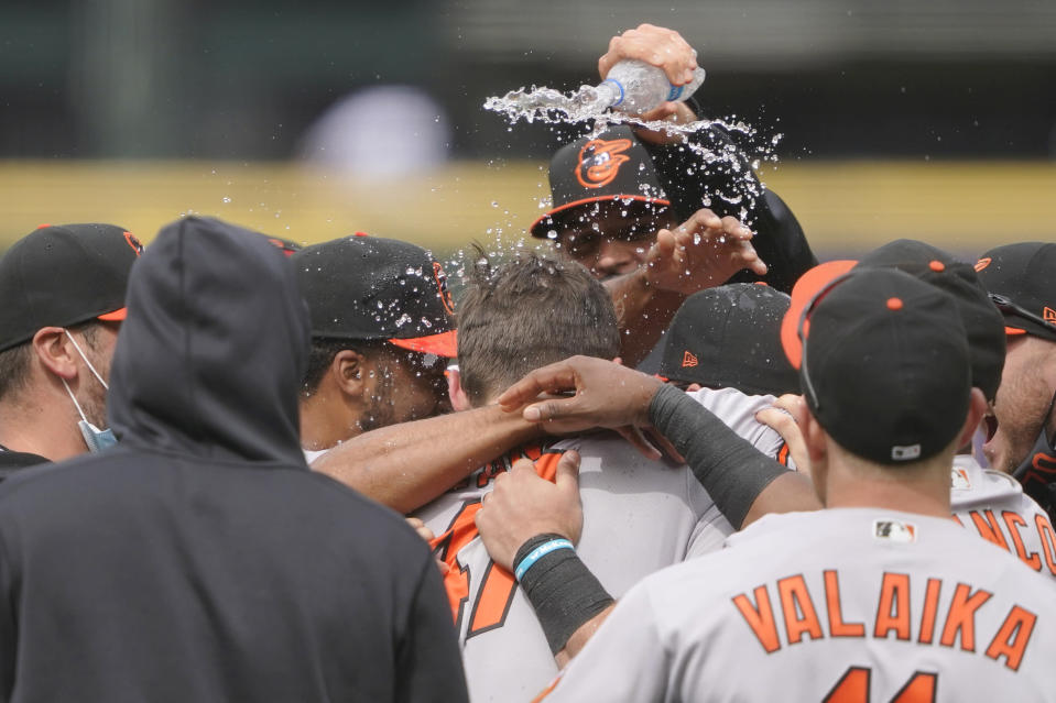 Baltimore Orioles starting pitcher John Means is mobbed by teammates and has water dumped on him after he threw a no-hitter baseball game against the Seattle Mariners, Wednesday, May 5, 2021, in Seattle. The Orioles won 6-0. (AP Photo/Ted S. Warren)
