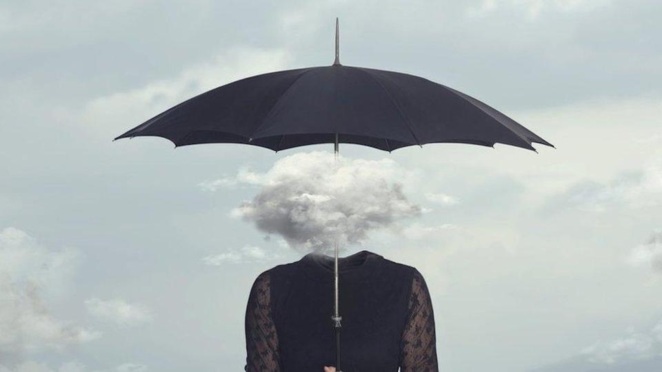 Concept image: A woman with a cloud for a head, holding an umbrella