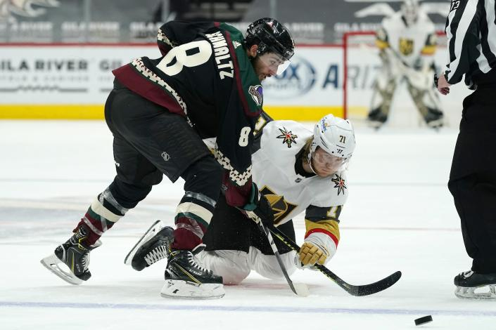 Arizona Coyotes center Nick Schmaltz (8) and Vegas Golden Knights center William Karlsson (71) battle for the puck during the second period of an NHL hockey game Friday, Jan. 22, 2021, in Glendale, Ariz. (AP Photo/Ross D. Franklin)
