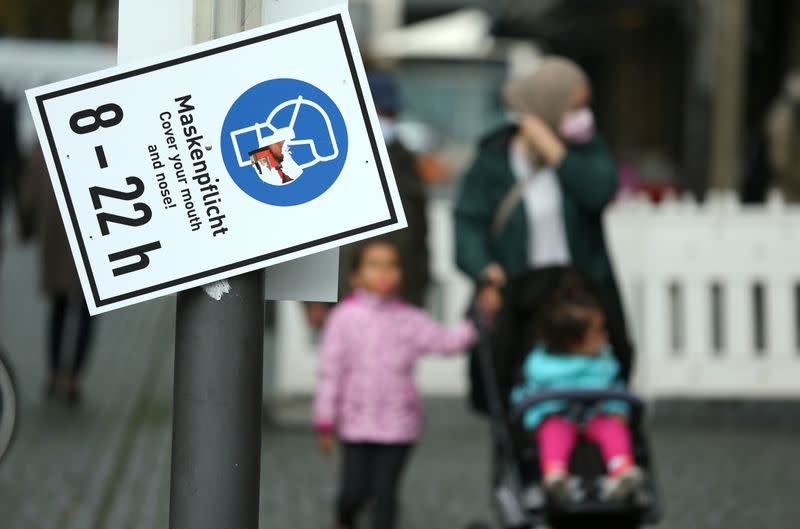 Pedestrians walk along a sign that reminds to wear a face mask as the coronavirus disease (COVID-19) outbreak continues in Frankfurt