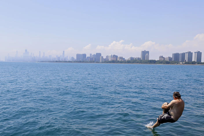 """Dan O'Conor, the """"Great Lake Jumper,"""" performs a can-opener dive on his 363rd leap as he nears his 365th consecutive daily plunge into Lake Michigan, Thursday, June 10, 2021, in Chicago's Montrose Point. (AP Photo/Shafkat Anowar)"""