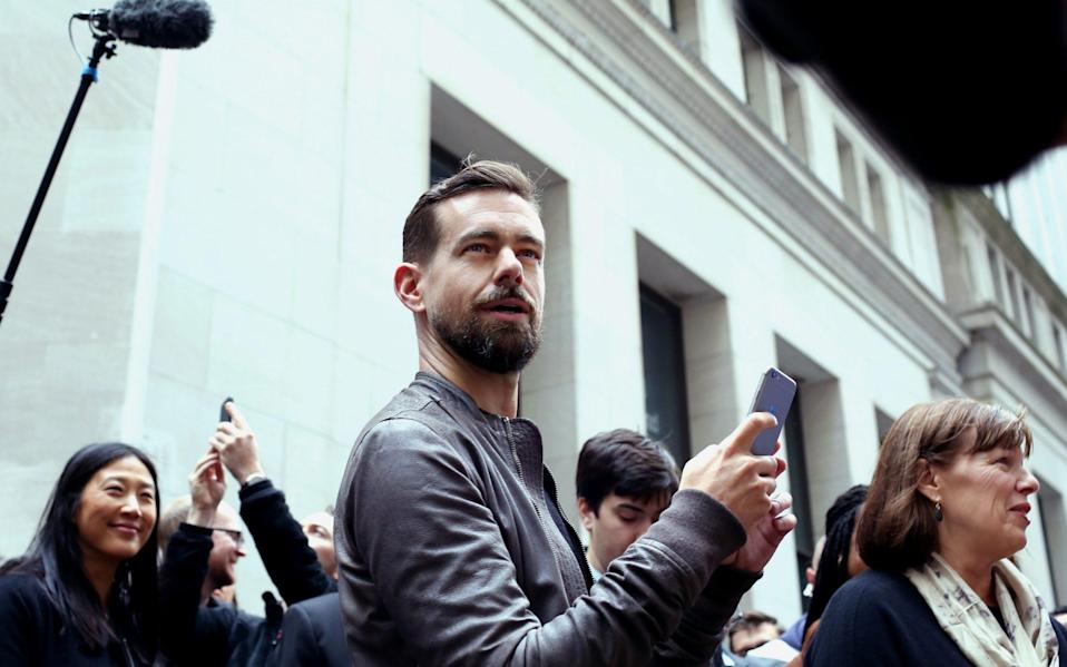 Jack Dorey, seen here as a younger man with a much neater, shorter beard and his hair swept back from a side parting, looks quizzically up away from his smartphone as he is surrounded by reporters and others outside the New York Stock Exchange - Yana Paskova/Bloomberg