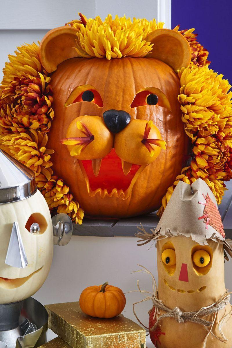 <p>This brave lion only looks hard to make. Hollow large pumpkin from base; carve mouth and eyes. Cut nose from a smaller pumpkin; paint black and let dry. Attach to large pumpkin with toothpicks. Halve and hollow a small orange pumpkin for snout; secure with wood skewers. Halve and hollow a small orange pumpkin for ears, cut flat on one side; secure with toothpicks. Straight-pin faux chrysanthemums around face for mane. </p>