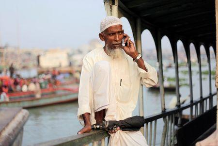 A man talks on the phone as he waits to board a boat by the river Buriganga in Dhaka
